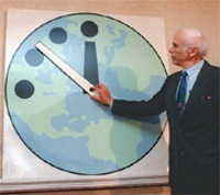 An elderly man in a suit adjusts the hand of the Doomsday Clock