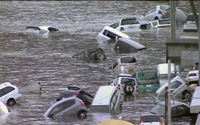 Vehicles float in the city streets, in the tsunami waters following the earthquake.